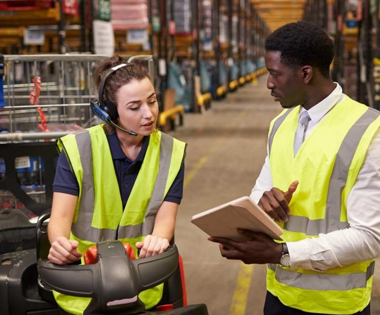 Two warehouse workers going over inventory