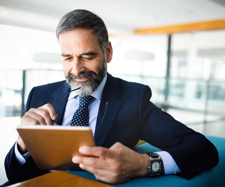 Man op tablet kijkt naar zijn geïntegreerde e-commerce oplossing